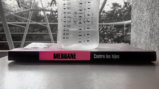 """Foto en blanco y negro en la que aparece a color únicamente el libro de Lina Meruane """"Contra los Hijos"""", bajo una mamadera con agua."""